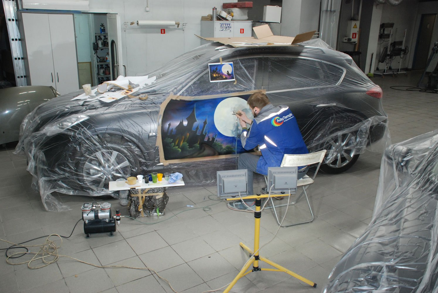 мастер рисует на машине