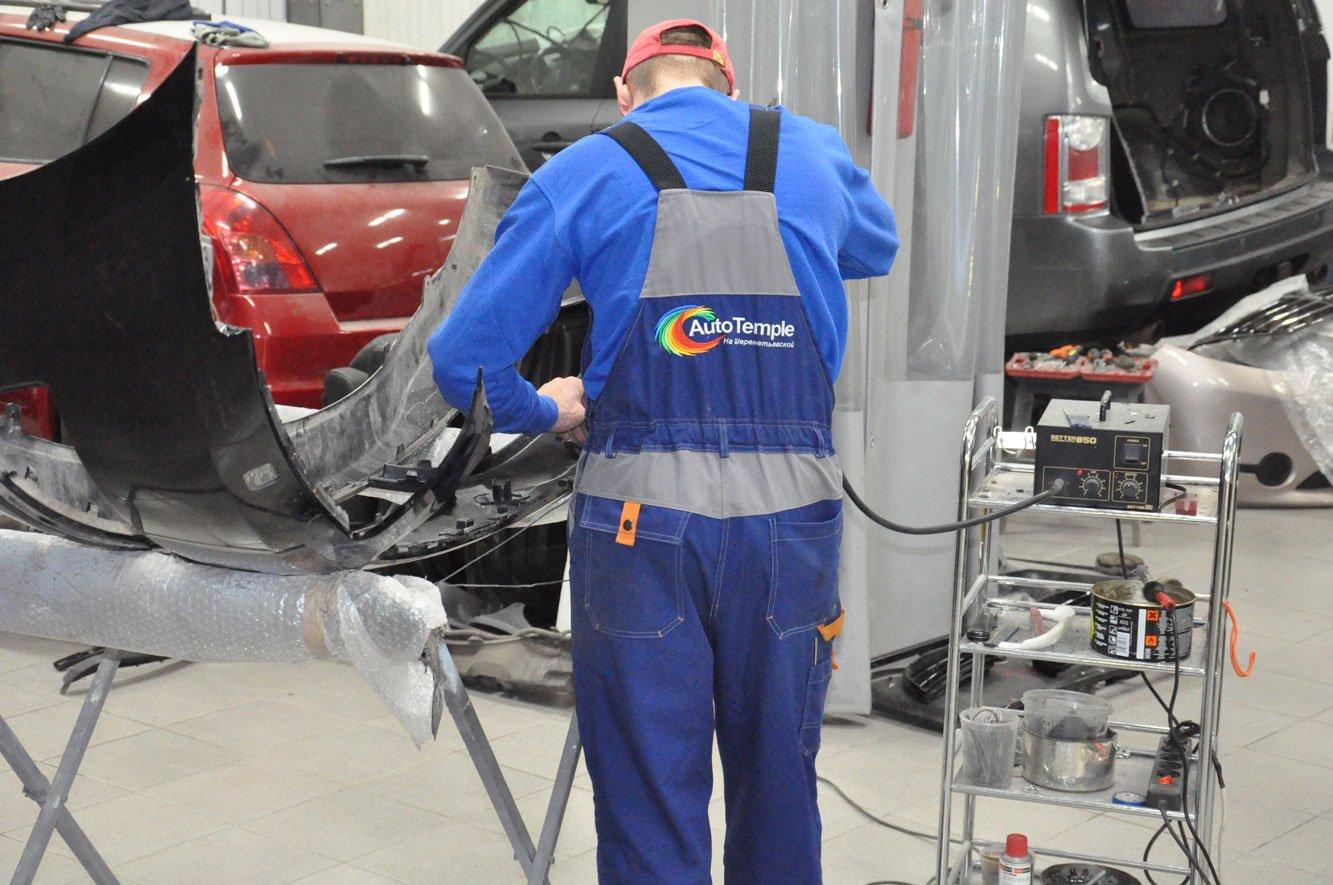 мастер в костюме ремонтирует машину в Москве