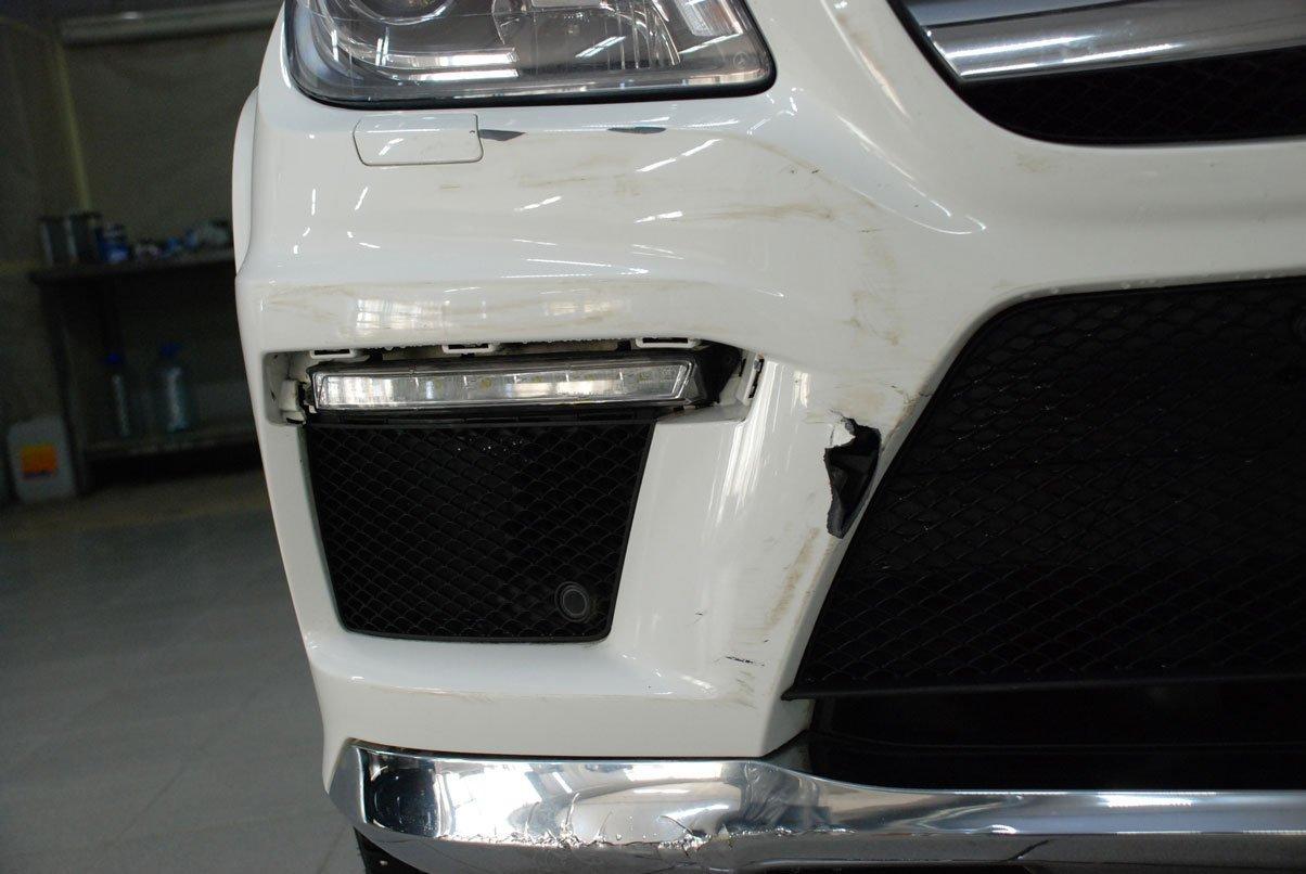 разбитый белый бампер на автомобиле
